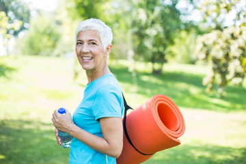 Senior woman holds fitness mat on her back in the park and preparing for exercise
