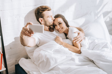 high angle view of beautiful young couple taking selfie with smartphone while relaxing in bed in morning