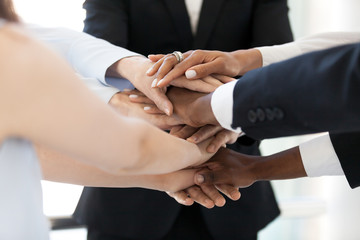 Close up of diverse employees stack hands in pile show mutual support, multiethnic workers promise loyalty and help involved in team building activity, team united at motivational business training