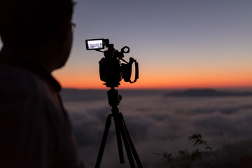 Cameraman and video camera operator working with his equipment shooting sunrise foggy landscape