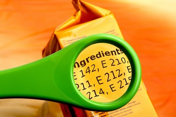 Concept of reading ingredients list on food package with magnifying glass. Magnifying glass on food additives label.