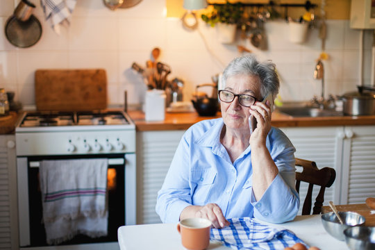 Senior woman is talking on mobile phone at cozy home kitchen. Grandmother has tea or coffee break in cooking. Retired person is using device. Concept of people cyber privacy, connection, communication