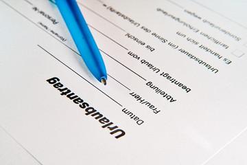 Urlaubsantrag eines Arbeitnehmers mit Kugelschreiber auf einem Tisch