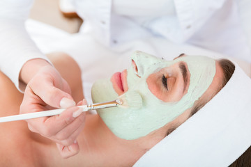 Close up of a beautician applying face peeling mask to woman