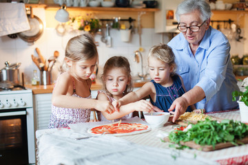 Family, kids cooking pizza in cozy home kitchen. Grandmother and three sisters, her granddaughters preparing homemade italian food. Funny little girls are helping senior woman. Children chef concept.