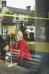 Woman looking through window while stirring coffee