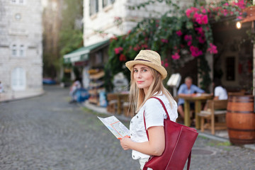 Girl traveler is using city map, searching italian authentic street restaurant. Woman tourist is exploring locations, walking in old town. Concept of travel, vacation, female tourism, adventure, trip