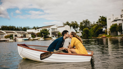 Couple on a date kissing in a boat