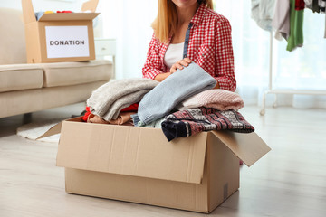 Woman packing clothes into donation box in living room