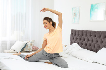 Young beautiful woman doing exercise on bed at home. Morning fitness