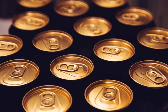 metal beer cans background black gold
