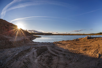 panorama near quarry flooded with water for sand extraction mining in the evening sun