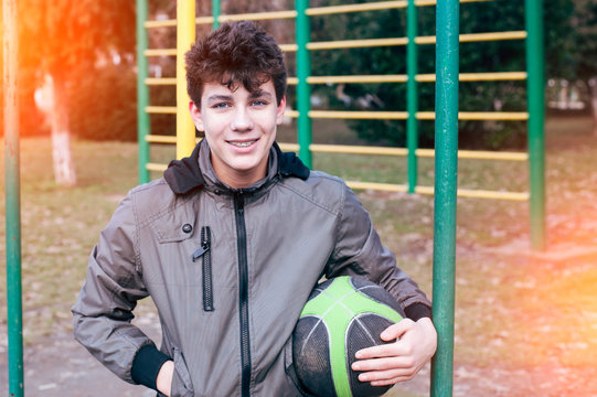 Happy teenager in a jacket and a basketball ball in his hand smiles at the background of a sports ground. A boy has braces for teeth equalizing