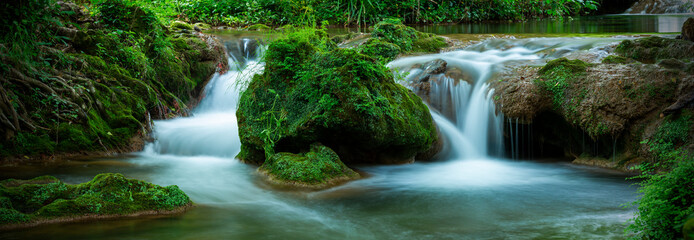 Small cascades with water flowing in the forest