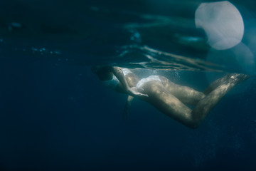 Wide shot of a woman swimming underwater