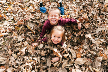 Autumn: Brother And Sister Playing In Leaf Pile