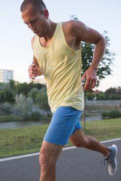 Portrait of fit caucasian man jogging outdoor in the evening