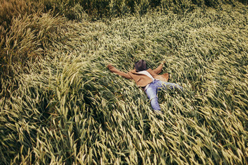 Rustic boy laying in the rye field