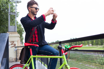 Stylish man in sunglasses with bike making photo via mobile phon