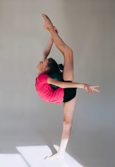 Gymnast girl exercising in white studio