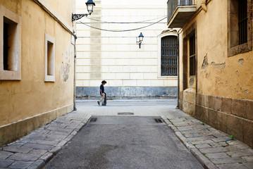 Skateboarder walking along the street.