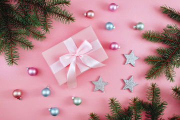 Christmas composition. Christmas gift, knitted blanket, pine cones, fir branches on pink background. Flat lay, top view, copy space