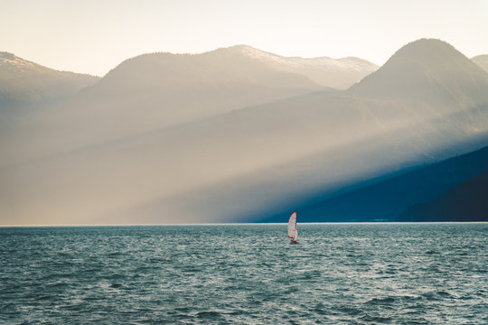 Small sailboat on the water in front of giant beams of light in the mountains
