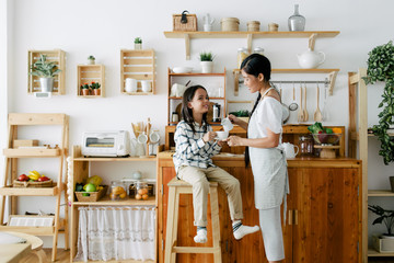 Mother and child making tea together in the wooden kitchen