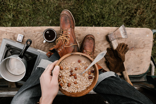 Anonymous  man holds wooden dish with oat meal and nuts in hand seated on the car wearing jeans and leather vintage boots having breakfast open space