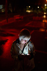 Woman in silver jacket using her phone lit by red light