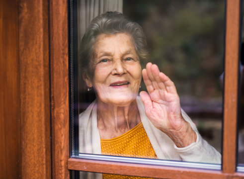 An elderly woman standing by the window, looking out. Shot through glass.