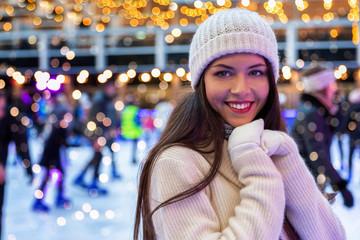 Attraktive Frau in winterlicher Kleidung hat Spaß auf einer Eislaufbahn zur Weihnachtszeit