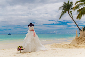 Wedding accessories. A mannequin in a wedding dress, and a Bridal bouquet on a tropical beach. Sea and palm trees in the background.