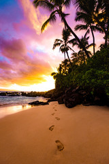 Peaceful Footprints in the Sand with Awesome Colorful Sky at Sunset and Calm Ocean Water Coming on Sandy Beach Shore with Palm Trees Silhouette and Lush Greenery at Secret Beach in Maui Hawaii