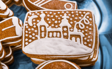 Close-up of a sweet Christmas gingerbread with a painted church. Traditional Xmas and New Year gingerbreads decorated by white frosting. Beautiful detail of yummy aromatic pastries stacked on a plate.