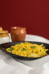 Traditional western Indian breakfast using rice flakes (flattened rice) called Aloo Pohe