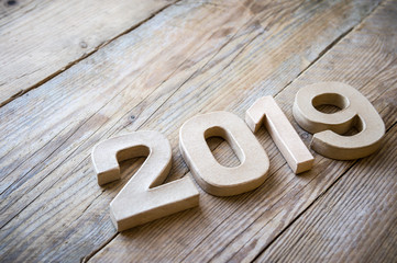 New Year 2019 message in plain brown cardboard numbers on natural weathered wood background