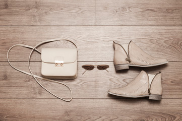 Trendy leather shoes, glasses, bag on a wooden background. Light beige color. Top view