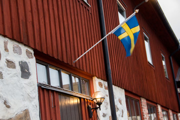 Traditional part of an old, historic and farm building of rural Sweden in Hassleholm during winter with Swedish flag.