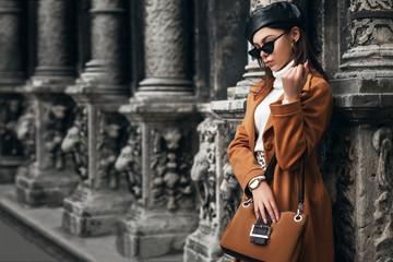 Outdoor fashion portrait of  elegant woman wearing sunglasses, leather beret, wrist watch, turtleneck, camel color coat, holding suede handbag, posing in street of european city. Copy, empty space