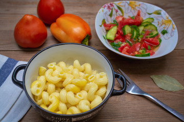 pasta and vegetable salad on a wooden table