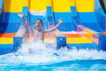 Cheerful boy splashing water on water slide at aqua park