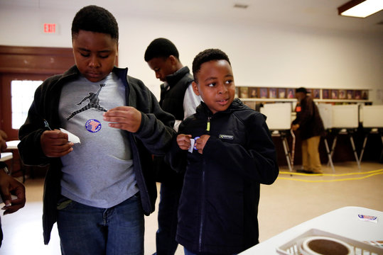 Brothers, Lamar Jackson, 10, left, Lamarion Jackson, 13, and Lamaven Jackson, 9, put future voter stickers on their shirts after watching their mother vote in the midterm elections at the Winterville Train Depot in Winterville