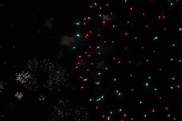 Fireworks in the night sky. Texture salute. Abstract photo of flares on a black background. Photos of lights salute in the sky. Image of salute flashes. Texture of colored lights.