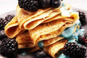 Delicious Tasty Homemade crepes or pancakes with blackberries,blueberries and blue spirulina nicecream.