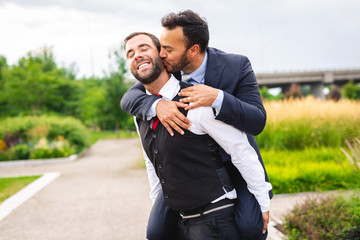 A Handsome gay male couple in the park on their wedding day