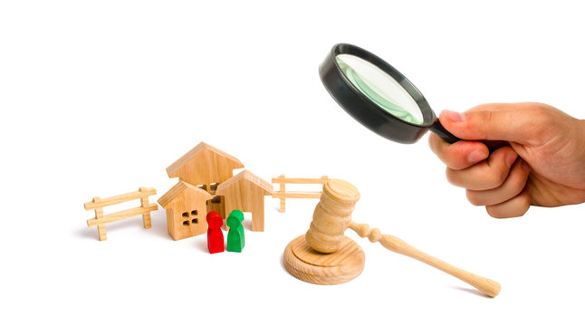 Magnifying glass is looking at the Wooden apartment house with people, keys and a judge hammer on a white background. The concept of laws and regulations for tenants and owners of a building. .