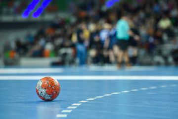 Match ball lying on the parquet near 9 m line.