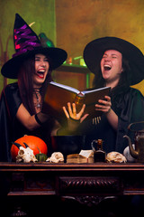 Photo of laughing two witches brunettes in black hats reading book of incantations