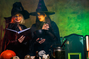 Picture of smiling two witches in black hats reading book at table with pumpkin and skulls